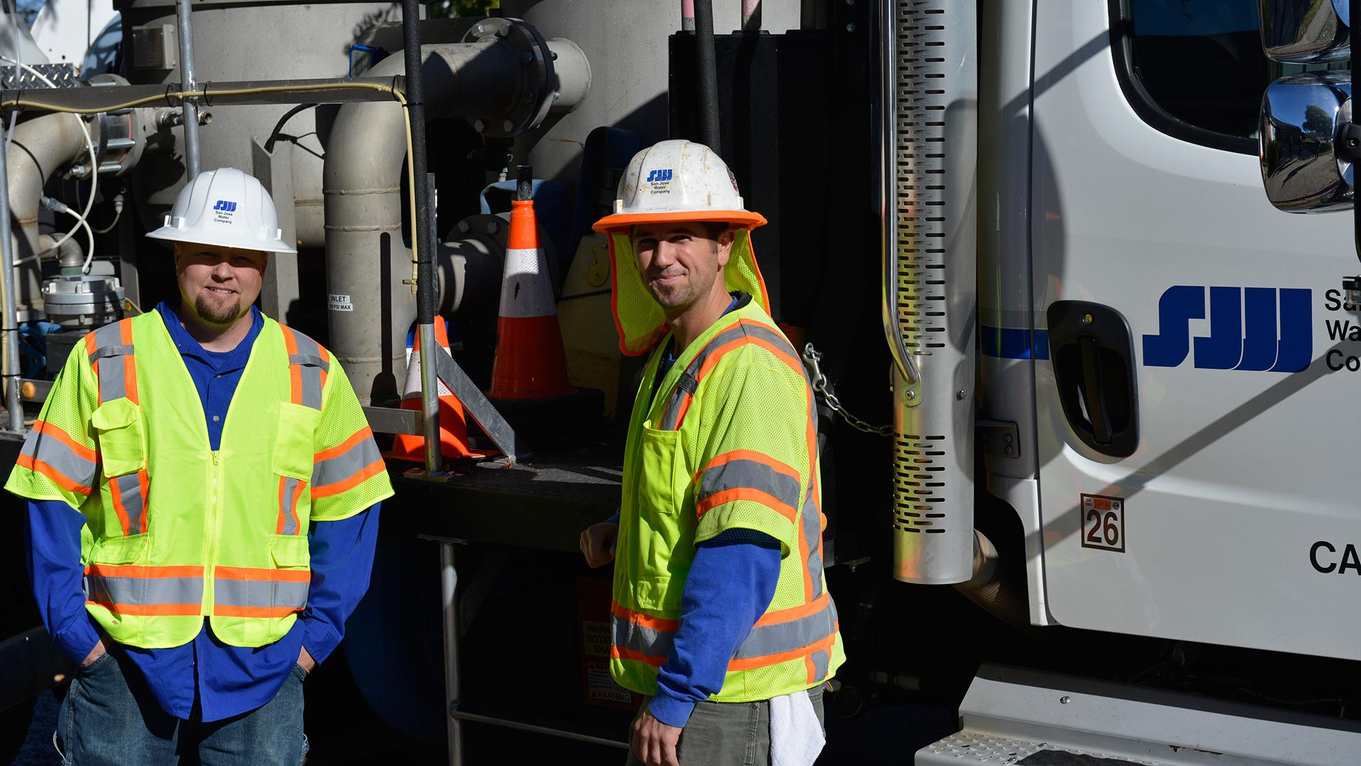 Two workers in hard hats and yellow vests in front of a company utility truck