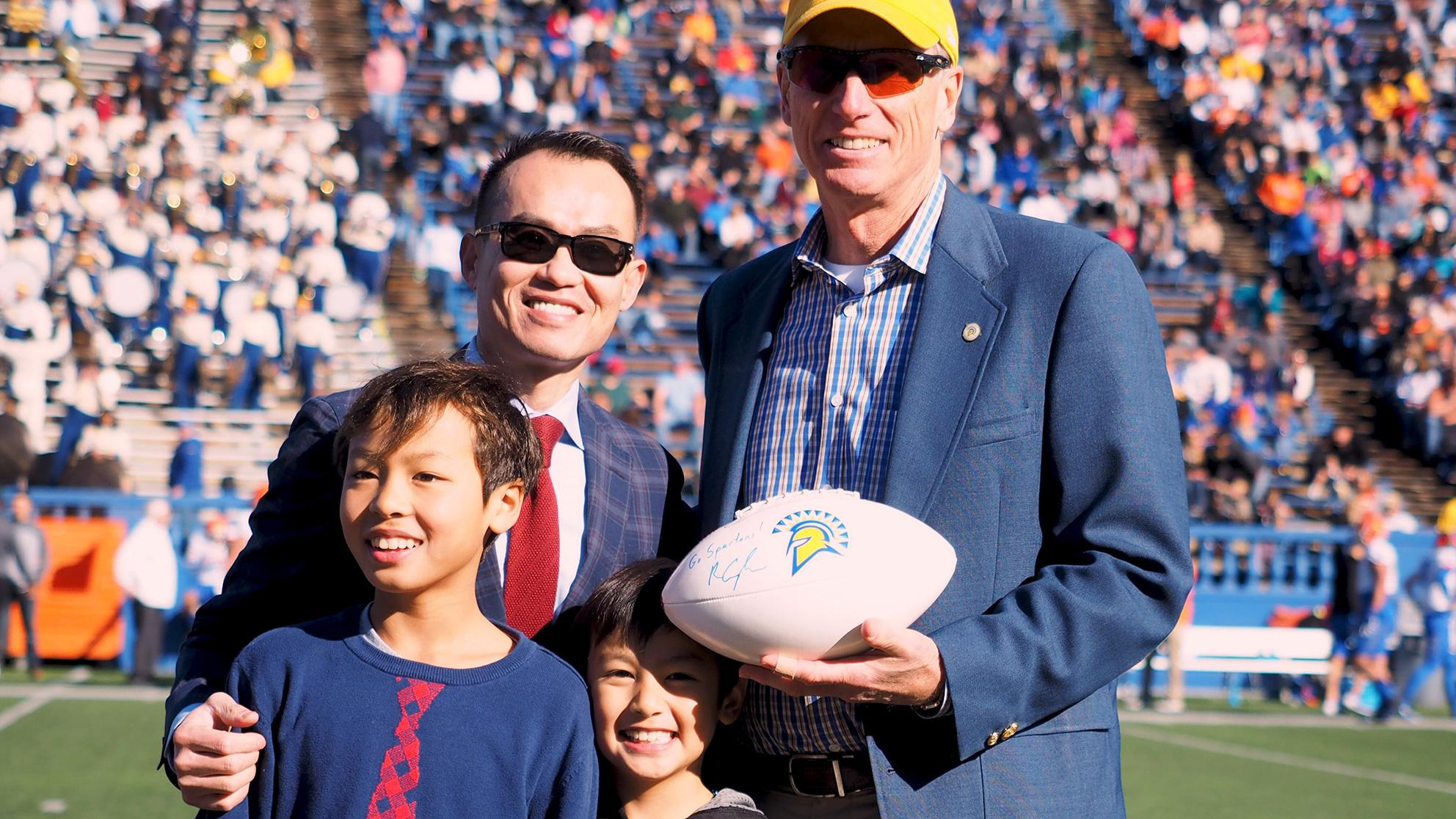 A father with his two young boys next to a tall man holding a football