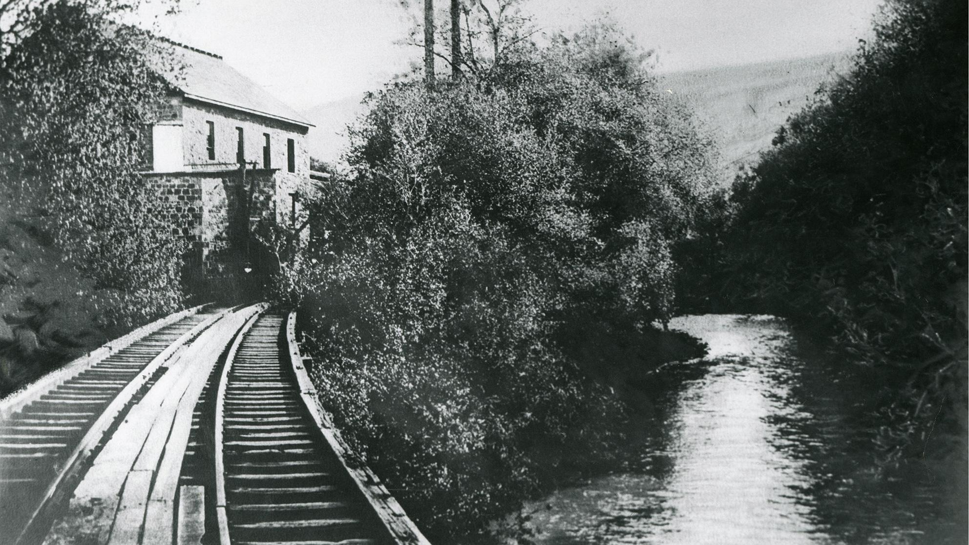 Archival black and white photo of train tracks along a river