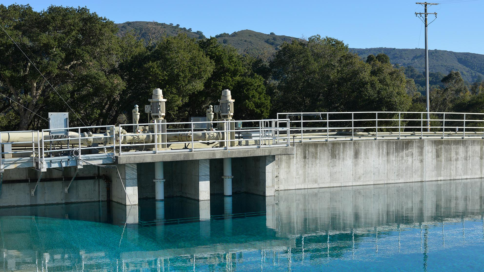 Water reservoir with green hills and blue sky in the background