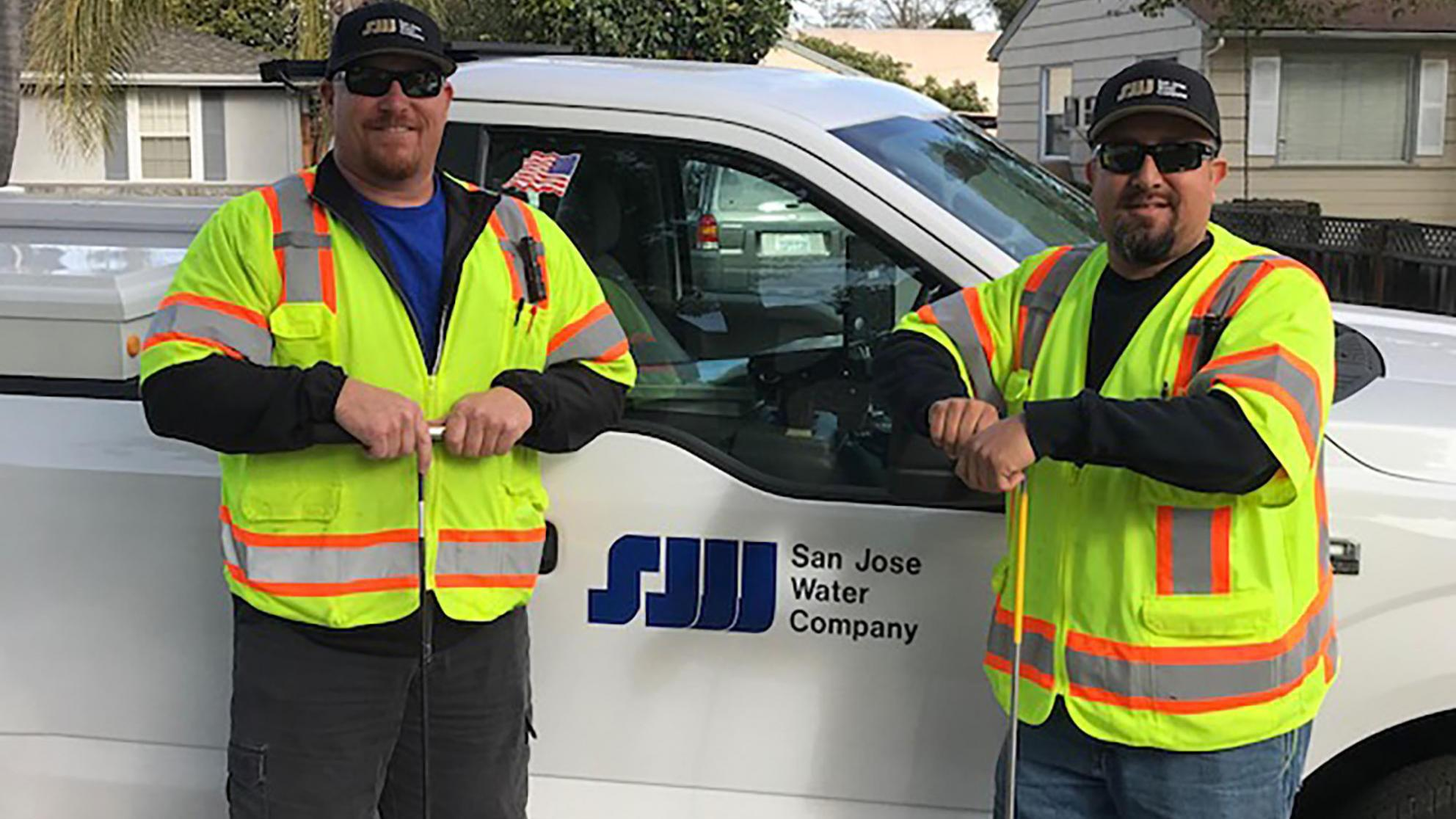 Two SJW employees standing in front of a work truck