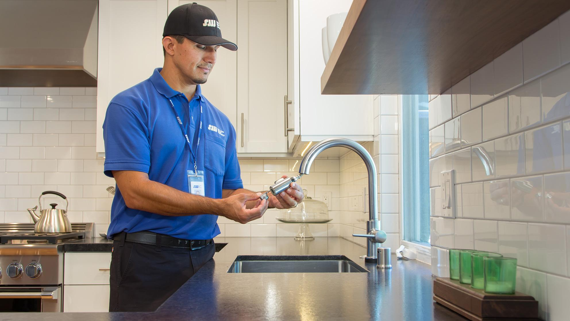San Jose Water worker examines kitchen faucet