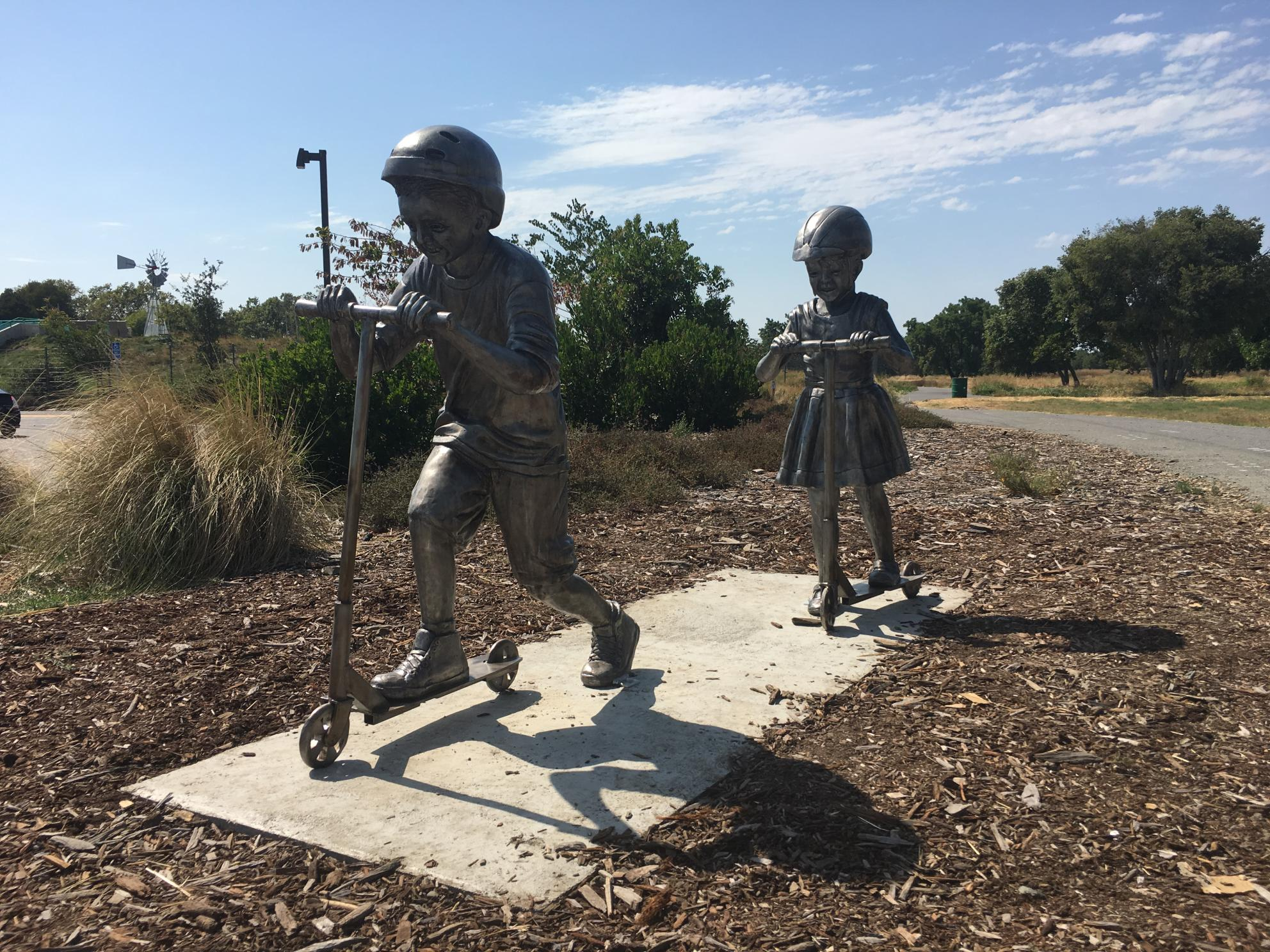 Children's Rotary Sculpture Walk Statues - Children on Scooters