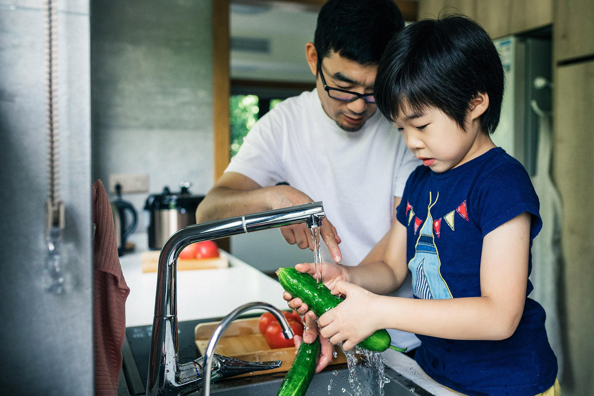 Father and daughter washing vegetables