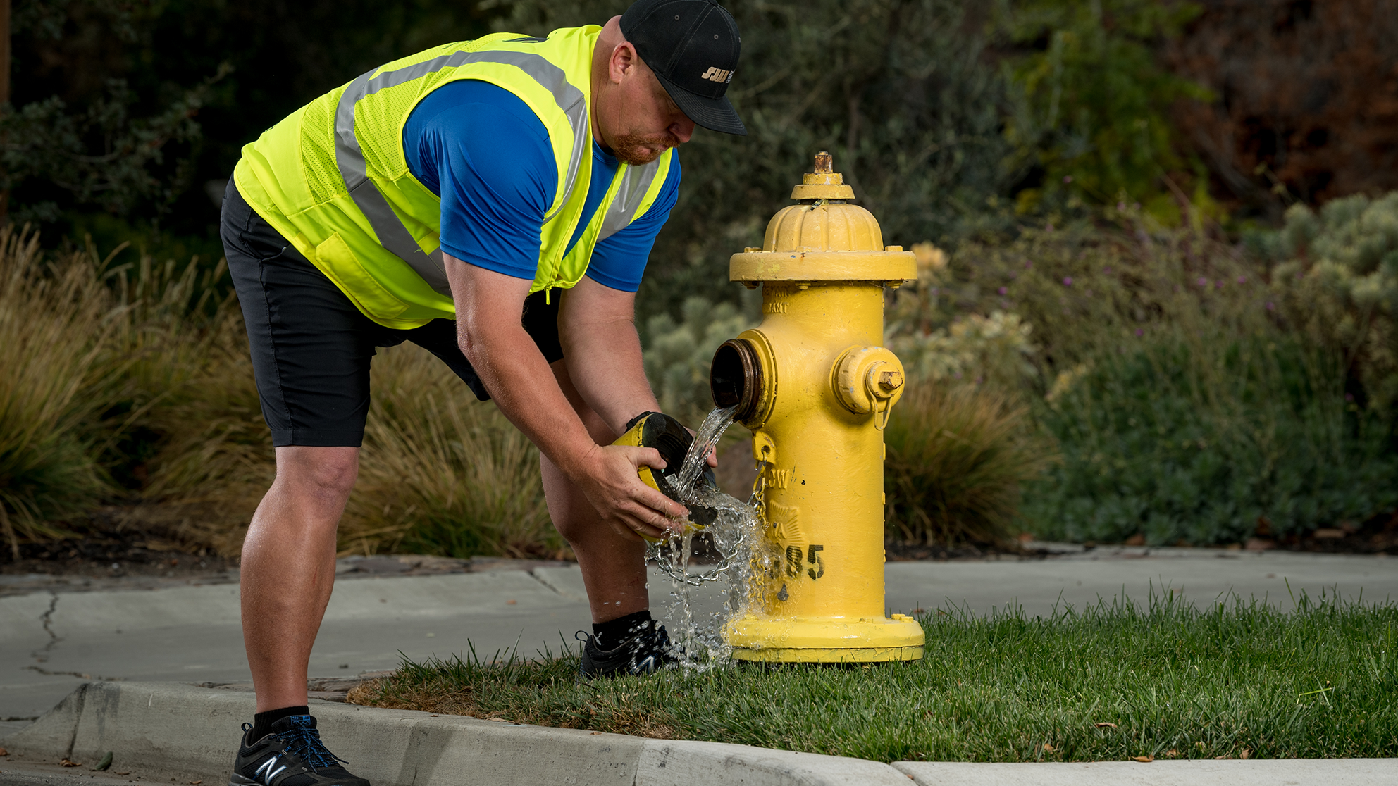 A San Jose Water employee removing the cap of a fire hydrant as some water leaks out.