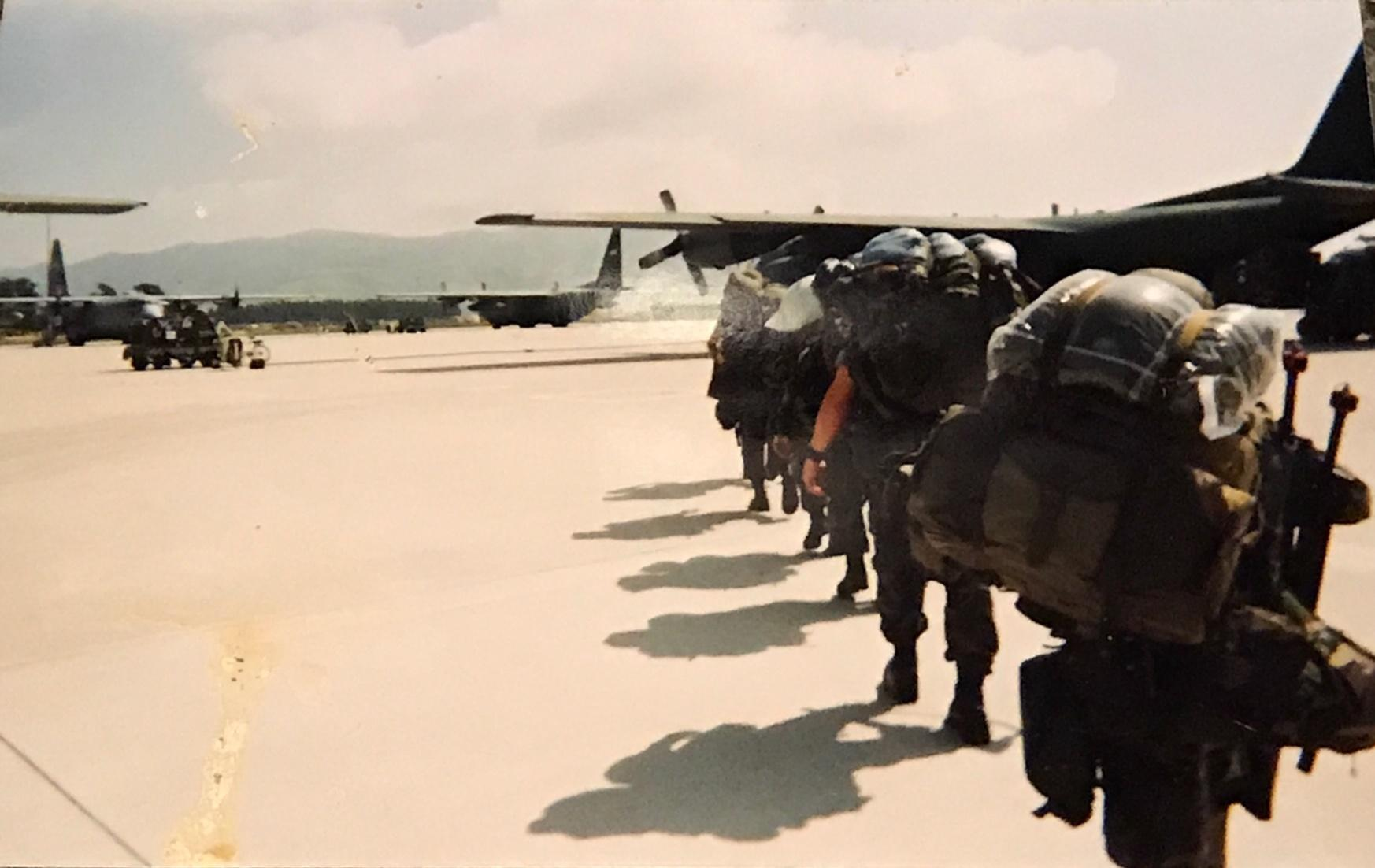 Air force soldiers on the tarmac walking towards a large military plane
