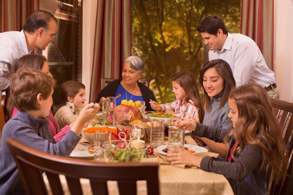 Multigenerational family at a dining table having dinner together