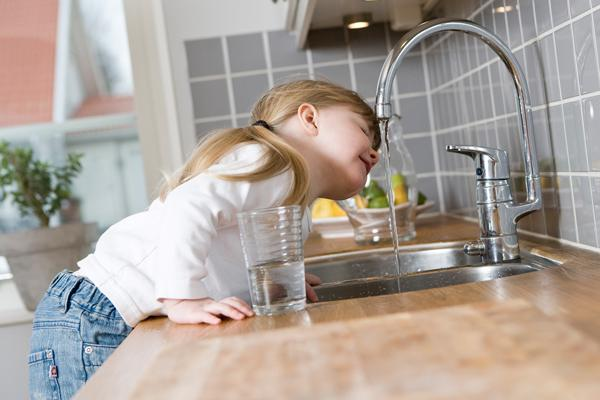 Little girl drinking water out of a kitchen faucet