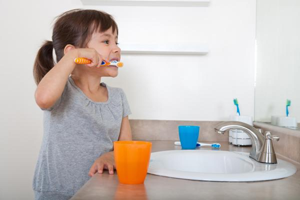 Little girl brushing her teeth with orange toothbrush and cup